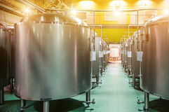Modern Beer Factory. Rows of steel tanks for the storage beer. Modern Beer Factory. Rows of steel tanks for the storage and fermentation of beer. Spot light Stock Photos