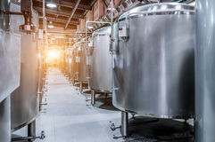 Modern Beer Factory. Small steel tanks for fermentation of beer. Modern Beer Factory. Small steel tanks for storage and fermentation of beer. Sunlight effect Stock Image