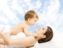 Modern behandla som ett barn lyckligt spela Barn i blöjan som omfamnar mamma över s Arkivfoto