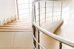 Modern beige office staircase with chrome handrails. Modern office marble shiny staircase with chrome banister royalty free stock image
