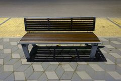 Modern bench on the sidewalk Royalty Free Stock Photos