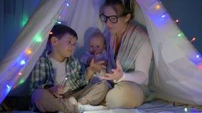 Modern berättar en saga och spelar med söner i vigvam med en dekorgirland i afton stock video