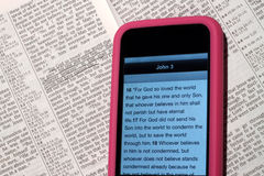 Modern Bible. On an electronic next to a traditional Bible where the scripture has been underlined. Both show the same passage of scripture, John 3:16, an stock photos