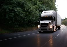 Modern big rig semi truck with guard and turn on headlights and. White modern big rig semi truck with grille guard and turn on headlights and reefer semi trailer Stock Images