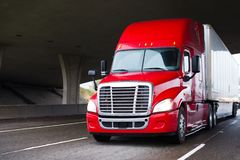 Bright red modern big rig semi truck with dry van trailer runnin Stock Photo