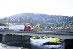 Modern big rig semi truck with semi trailer moving on the bridge. Modern red big rig semi truck with reefer semi trailer transporting commercial cargo and moving stock image
