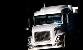 Modern big rig white semi truck in dark shadow. Big powerful white bonneted rig semi truck illuminated by the sun moves with commercial cargo towards the light Royalty Free Stock Image