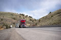 Modern big rigs convoy moving on the road between the hills in I. Big rig American classic and modern fleet semi trucks convoy with semi trailers going on Stock Photos
