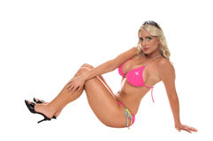 Modern Bikini Pinup. Blond bikini pinup model in a pink bikin. sitting on the floor in a classic pinup pose stock photo