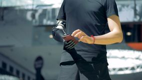 Modern bionic hand in use, close up. A person with an artificial robotic hands uses his phone, typing. A person with an artificial robotic hands uses his phone
