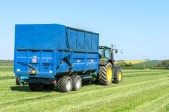 Modern blå traktor som drar en släp i gräsfält Arkivfoto