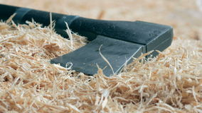 Modern black axe lies in a large pile of sawdust. Close-up of the cutting part of the Axe. moving the camera stock video footage