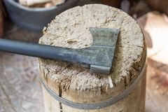 Modern black axe in the log and wooden chips after cutting firewood for winter near pile wooden house Royalty Free Stock Image