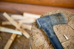 Modern black axe in the log and wooden chips after cutting firewood for winter near pile wooden house Stock Photos
