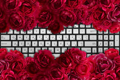 Modern black and chrome laptop keyboard with bush of red rose flowers Stock Images