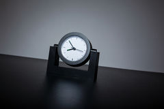 Modern black clock on black table in the office. Gray background Stock Photography