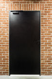 Modern black door in a brick wall Royalty Free Stock Photo