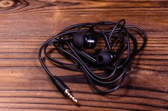 Black earphones on wooden table stock photography