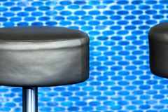Modern black leather barstool in front of blurred, vigorous-blue Stock Photo