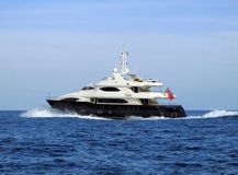 Modern black MY. Modern black medium sized Motor yacht 3/4 view at speed Royalty Free Stock Photos