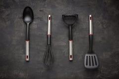 Modern Black Plastic Kitchen Utensils on Dark Background. Modern Black Plastic Kitchen Utensils on Dark Stone Background stock photo