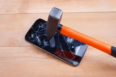 A smartphone hits a hammer and smashes the screen. The concept of electronics repair. Close-up. A modern black smartphone hits a construction hammer and smashes Royalty Free Stock Photo