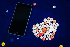Modern black smartphone with sewing buttons in the shape of a heart. On a retro blue background Royalty Free Stock Images