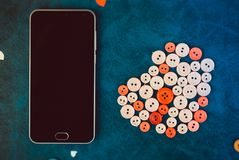 Modern black smartphone with sewing buttons in the shape of a heart. On a retro blue background Stock Photos