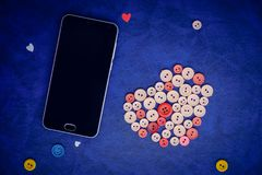 Modern black smartphone with sewing buttons in the shape of a heart. On a retro blue background Royalty Free Stock Photos