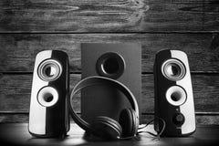 Modern black sound speakers. And headphones on dark background stock image