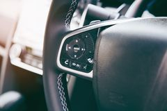 Modern black steering wheel with multifunction buttons for quick control, close-up in the car stock image