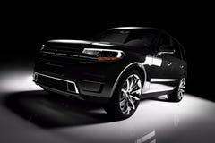 Modern black SUV car in a spotlight on a black background. Stock Photos