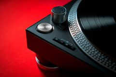 Modern black turntable on a red background. Closeup on a modern black turntable on an intense red background Stock Photos