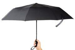 Modern black umbrella in handon white background. Stock Photos