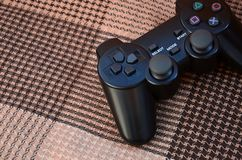 Modern black video game controller lies on a checkered beige and black veil or plaid. Plastic joystick as a concept for children stock photography