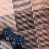 Modern black video game controller lies on a checkered beige and black veil or plaid. Plastic joystick as a concept for children` royalty free stock image