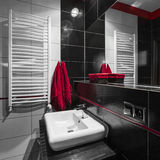 Modern black and white bathroom. Modern bathroom in black and white tiles with red decorations Stock Photos