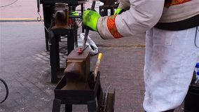 Modern blacksmith in capital demonstrates their ability to manufacture fasteners at Christmas fair stock footage