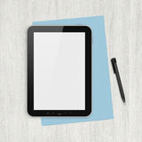 Blank digital tablet on a white desk. Modern blank digital tablet, papers and pen on a blank wooden desk. Top view. High quality detailed graphic collage Royalty Free Stock Image