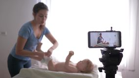 Modern blogger work, young mother blogger changes nappy to small baby boy while recording training video for subscribers stock footage