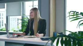 Elegant woman working in stylish office. Modern blond woman in trendy suit sitting at table in light contemporary office. Modern blond woman in trendy suit stock video footage