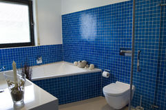 Modern Blue Bathroom. Modern bathroom with blue tiles, stylish basin, bathtub and shower Stock Images