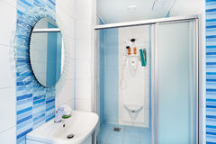 Modern blue bathroom interior with round mirror Stock Photos