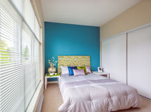 Modern blue bedroom interior design. Modern blue bedroom interior with blue,  green, and violet designer pillows in a luxury house. Interior design Stock Photos