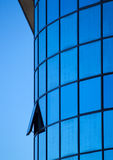 Modern blue building. A modern building with reflections from the sky and an interesting opened window stock photos