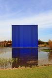 Modern blue building reflecting in water Stock Images