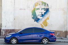 Modern blue car in front of Che Guevara wall painting, Havana, Cuba royalty free stock images