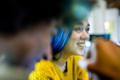 Modern blue hair woman smiling.Group of multiethnic people having business team meeting in restaurant lounge.Teamwork. Modern blue hair women smiling.Group of royalty free stock images
