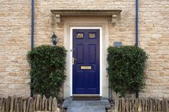 Front door. Modern blue painted front door flanked by shrubs stock images