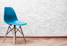 Modern blue plastic chair in an empty room with wooden floor on gray Brick Wall Background. With copy space royalty free stock images